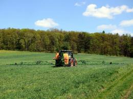 Equipment spraying pesticides or herbicides on farm field