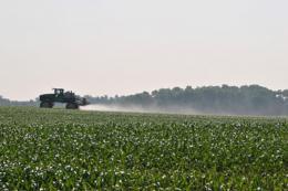 Spraying applying pesticides to farm field