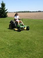 Young girl driving a lawn mower