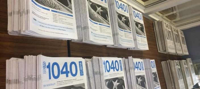Photo of IRS tax preparation form 1040 books stacked on table