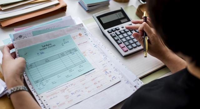Woman sitting at a desk with a stack of invoices and a calculator.