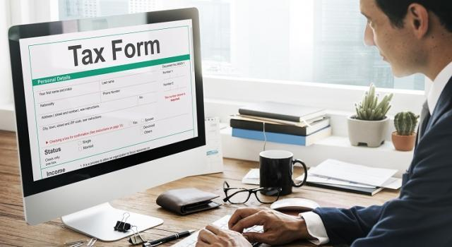Person sitting at a desk with a tax form on the computer screen
