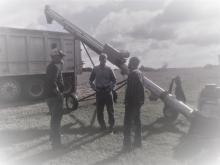 Group of agricultural workers standing in front of a grain cart.