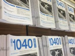 Photos of IRS 1040 publication booklets stacked on a table